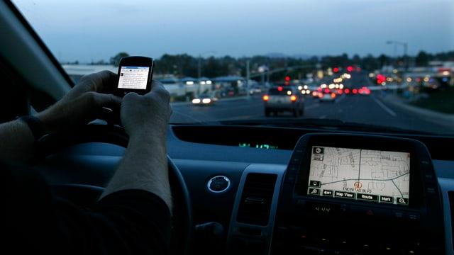 Jemand bedient ein Smartphone während des Fahrens, das Navigationsgerät leuchtet in der Dämmerung.