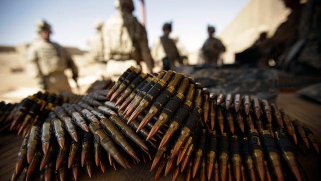 Munition liegt im Vordergrund auf einem Tisch, im Hintergrund vier amerikanische Soldaten mit Helm.