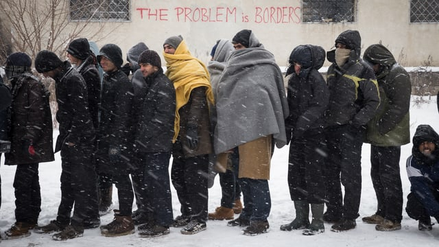 Männer stehen in einer Reihe im Schneetreiben, einige sind mit Wolldecken vermummt.