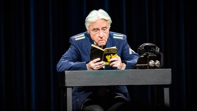 Emil sitzt am Tisch und liest in einem Buch.