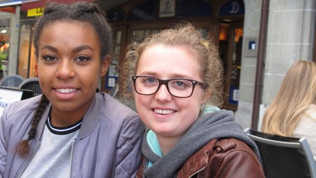 Die beiden jungen Damen lachen in die Kamera.