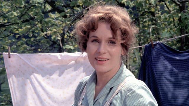 Eine lächelnde Frau. Im hintergrund sind Bäume und aufgehängte Wäsche zu sehen.