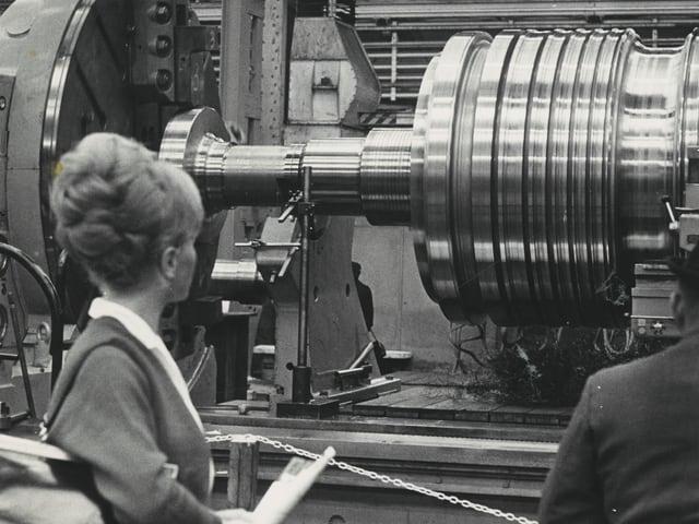 Eine Frau schaut eine technische Anlage an.