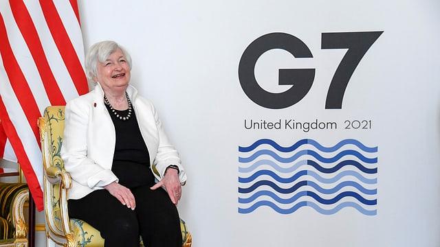Frau, die lacht, vor einer US-Fahnen und dem Logo der G7.