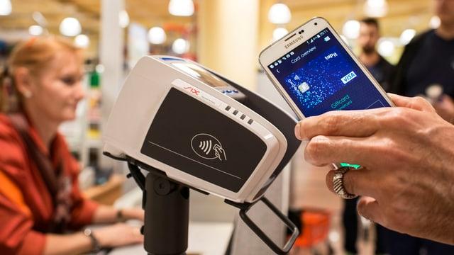 Eine Hand hält ein Handy an eine Kasse.