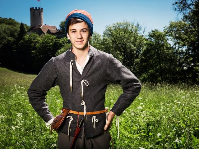 Junger Bursche in mittelalterlicher Kleidung auf einer Wiese mit einer Burg im Hintergrund