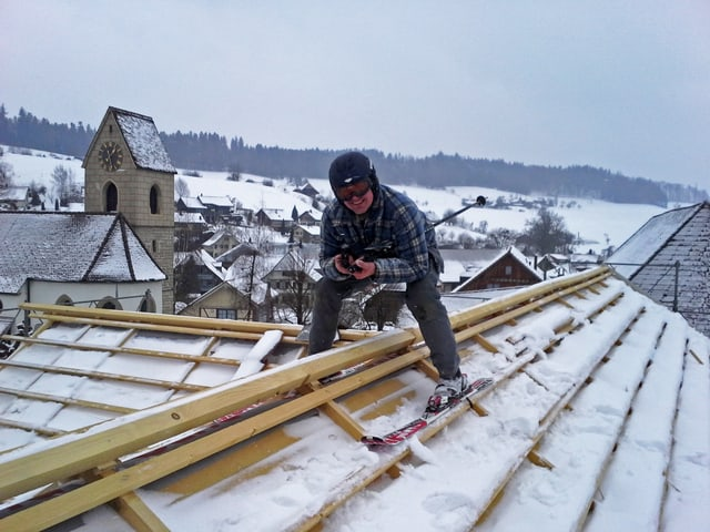 Oliver Zaugg mit Ski auf dem Dach.