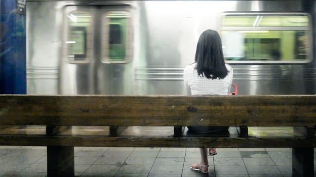 Eine Frau wartet auf einer Bank. Sie scheint auf die U-Bahn zu warten.