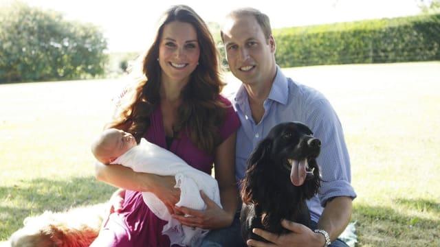 Kate mit Baby George auf dem Arm, daneben William mit einem Hund