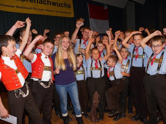 Die jungen Sänger werfen jubelnd ihre Hände in die Höhe.