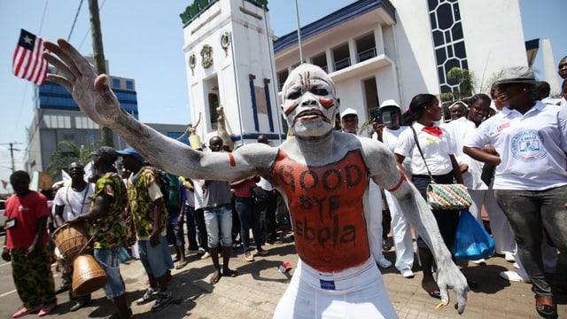 Ein weiss-rot angemalter Mann im Vordergrund, dahinter weitere Menschen und die liberianische Flagge.