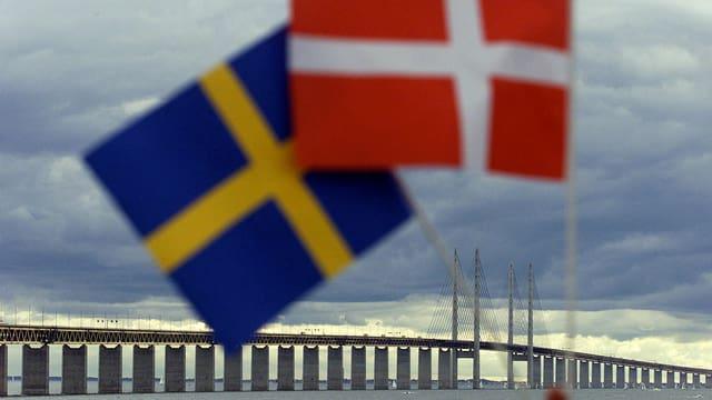 Schwedische und dänische Flaggen, dahinter die Öresund-Brücke.
