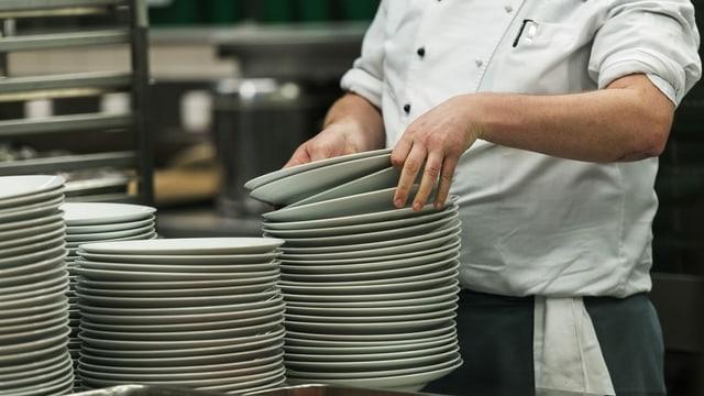 Ein Hotelangestellter wäscht Teller