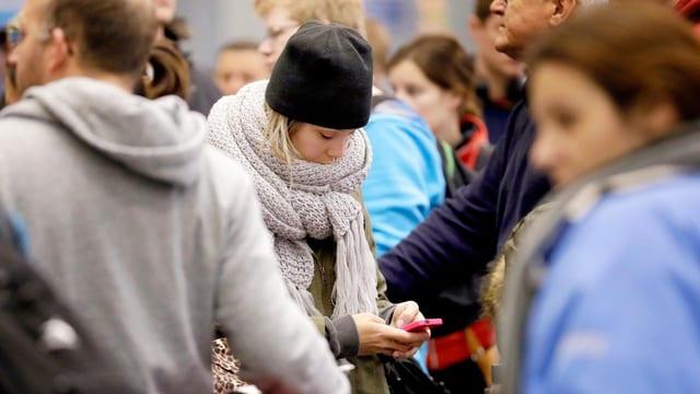 Eine Frau steht mit ihrem Smartphone in der Mitte einer Menschenmenge