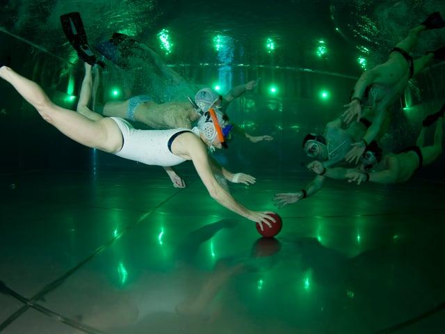 Frauen und Männer unter Wasser beim Rugby.