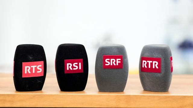 Il maletg mussa 4 microfons cun ils logos da las 4 unitads da la SRG SSR.