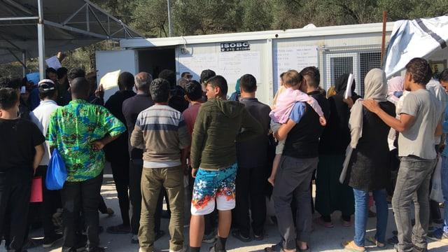 Mehrer Menschen stehen vor einem Gebäude in einem Flüchtlingscamp an.