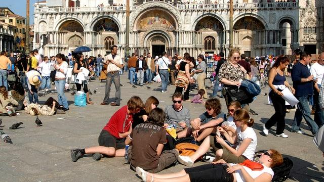 Touristen sitzen auf dem Markusplatz in Venedig