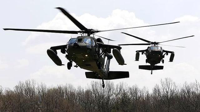Zwei amerikanische Kampfhelikopter schweben über Buschland.