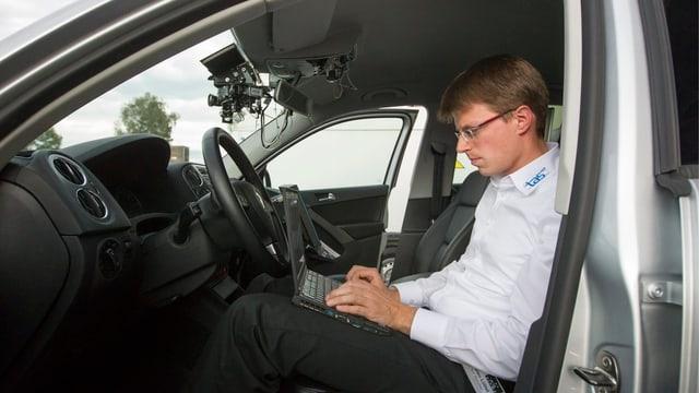 Ein Mann sitzt in einem Auto und programmiert das Robotersystem.
