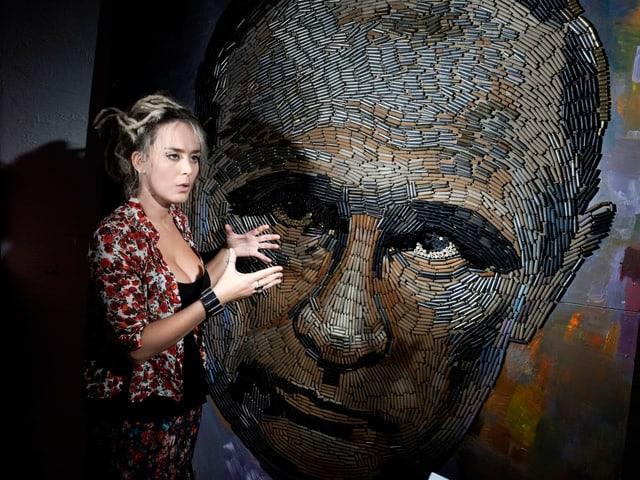Künstlerin vor Putin-Porträt.