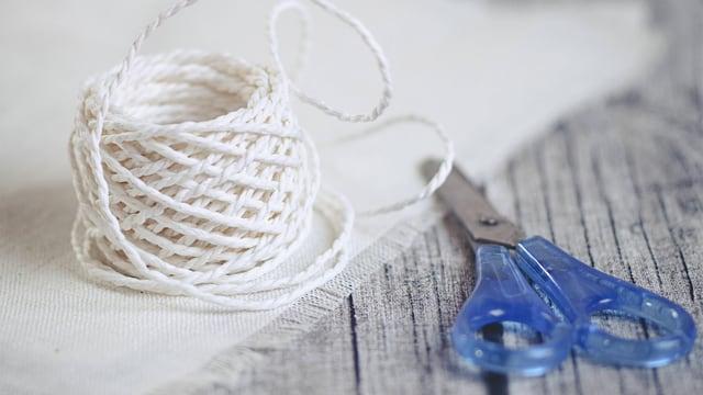 Eine weisse Rolle Schnur, deren Ende zum Teil ausgewickelt ist, liegt neben einer blauen Schere.