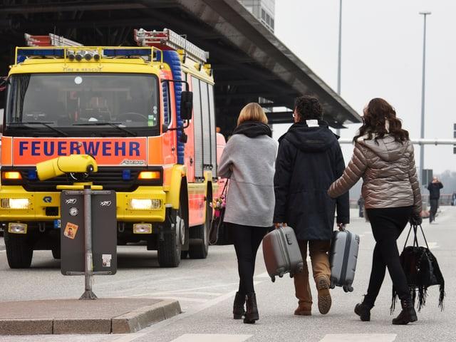 Menschen mit Koffern vor dem Hamburger Flughafen. Im Hintergrund Feuerwehr-Autos.