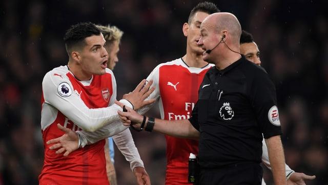 Granit Xhaka diskutiert wild gestikulierend mit dem Referee.