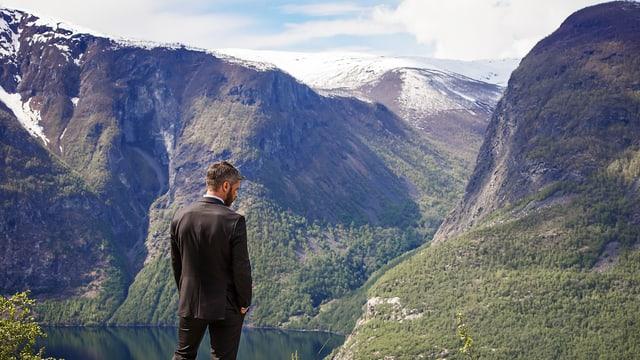 Aksel (Nicolai Cleve Broch) steht mit dem Rücken zur Linse vor einer nordischen Naturidylle.