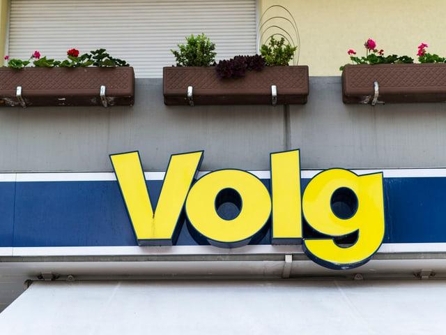 Volg-Logo unter einem Balkon mit Pflanzenkübeln.