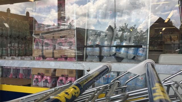Wasserflaschen hinter einem Schaufenster, davor Postiwägeli