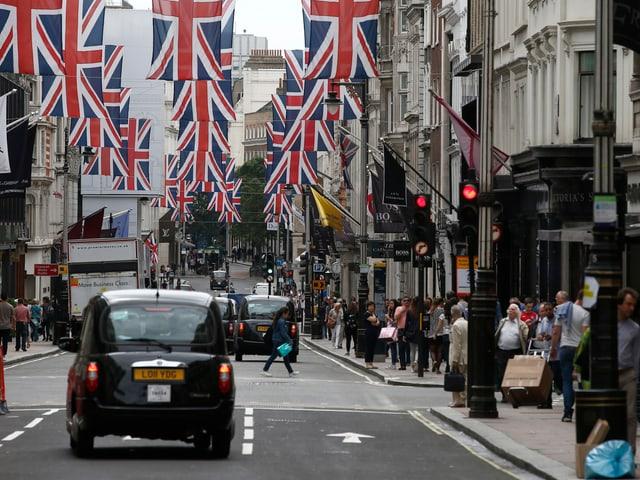 New Bond Street in London, schwarze Taxis auf der Strasse, Union Jacks hängen über der Fahrbahn.