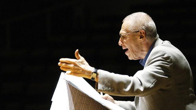György Kurtág hält eine Partitur in den Händen und gibt Anweisungen.