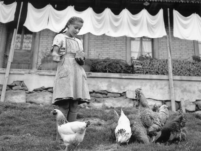 Ein Mädchen steht vor einem Bauernhaus und füttert Hühner, die im Garten sind.