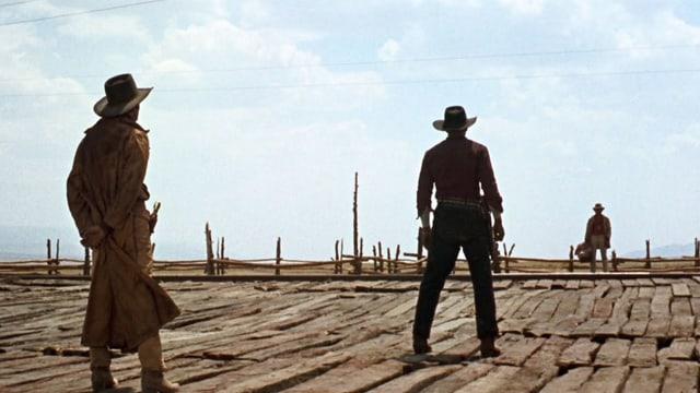 Western-Szene: Drei Männer stehen in der Einöde.