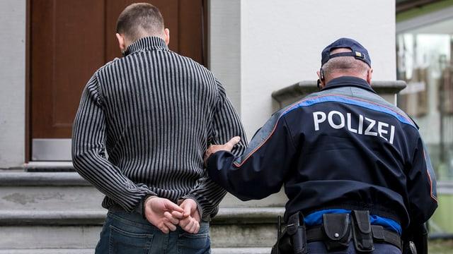Ein Mann wird in Handschellen von der Polizei geführt.