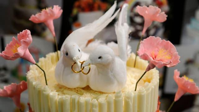 Hochzeitstorte mit zwei Tauben, die Eheringe in den Schnäbeln halten.