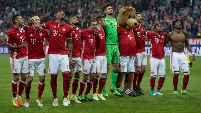 Die Bayern samt Maskottchen Bernie feiern in der Allianz Arena vor der Fankurve.