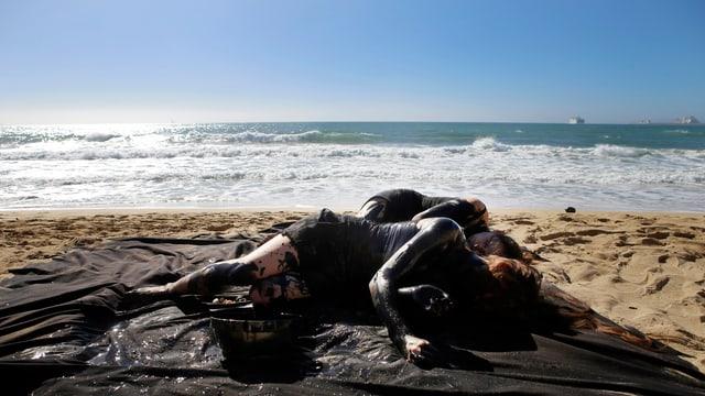 Zwei schwarz bemalte Personen liegen an einem Traumstrand auf Mallorca, die Sonne scheint.