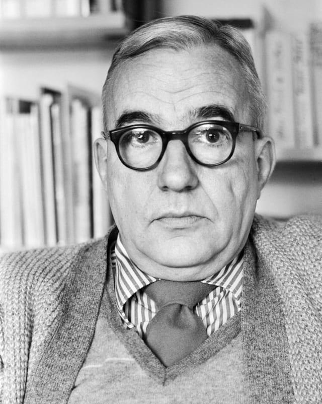 Schwarz-Weiss Bild von einem älteren Herr mit dunkler, dicker Brille