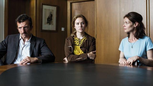 Ein Mann und zwei Frauen sitzen am Tisch