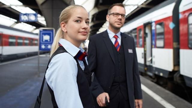 Ein Mann und eine Frau in SBB-Uniform stehen auf dem Perron vor einem Zug.