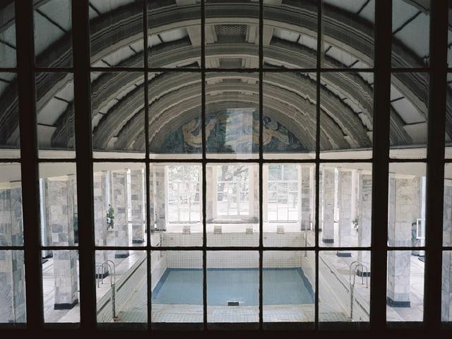 Blick durch ein Fenster auf ein Hallenbad mit verzierter, gewölbter Decke.