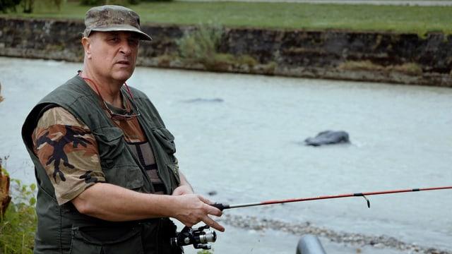 Ein Mann in Tarnkleidung beim Fischen.