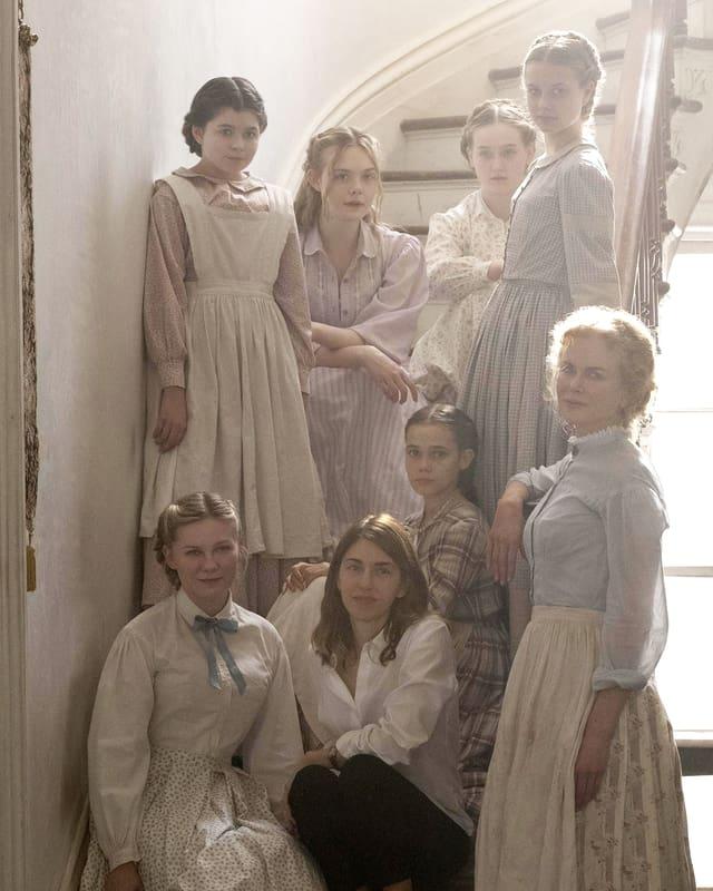 Die Regisseurin Coppola sitzt auf einer Treppe. Die Darstellerinnen umrahmen sie.