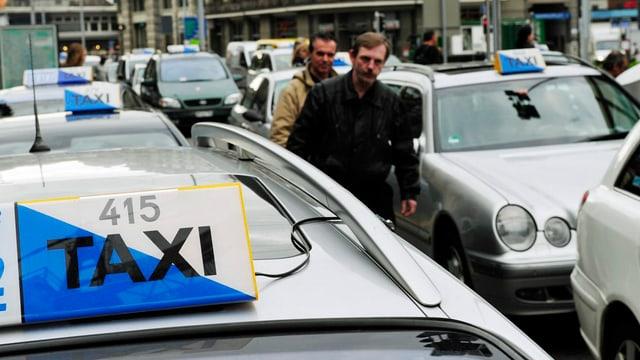 Zürcher Taxis warten in zwei Reihen vor dem Zürcher Hauptbahnhof auf Kunden.