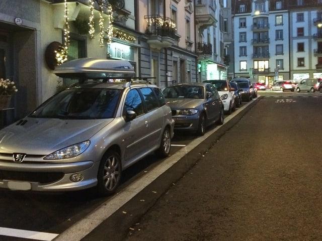 Eine Reihe von Autos, die bei Dämmerung auf weissen Parkfeldern parkiert sind.