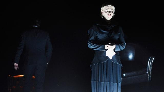 Eine Frau steht auf der Bühne. Ihr Gesicht ist beleuchtet.