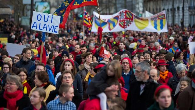 Demonstrationszug mit Flaggen und Schildern.