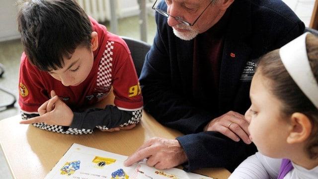 Älterer Mann liest zusammen mit zwei Kindern in einem Buch.